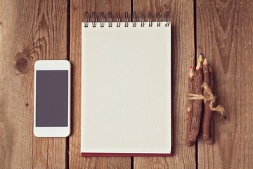 Blank notepad with smart phone and pencils on wooden table