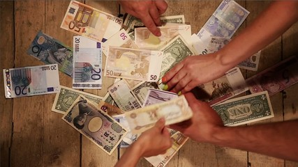 lot of currencies are taken by many hands on a wooden background