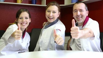 care attendants holding thumbs up, laughing to the viewer