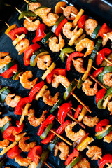 shrimp kebabs on black baking, diagonally