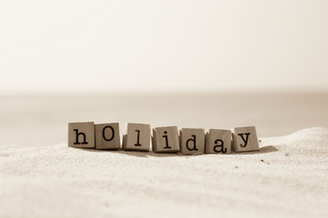 Holiday season word with sand beach background in sepia tone