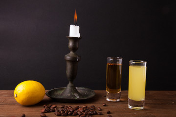 Two different drink on a wooden table with a candlestick.