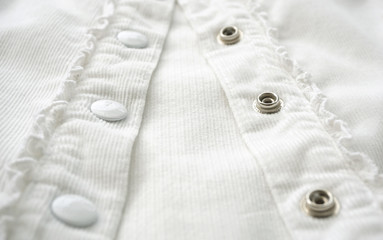 metal buttons on white shirt close up