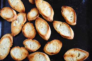 Crispy baked baguette slices on a baking tray