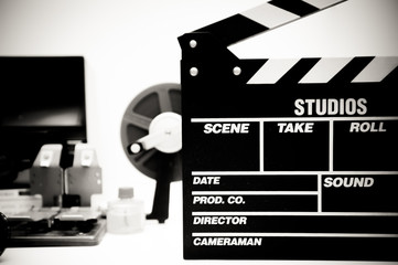 Clapper board with vintage movie editing desktop in black and wh