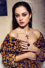 woman with dark hair wearing leopard print dress and bijou