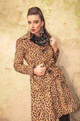 Elegant fashion woman posing near a wall