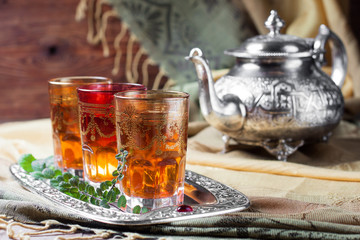 Moroccan mint tea in glasses on a tray and kettle