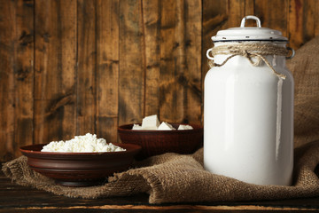 Milk can with cottage cheese on rustic wooden background