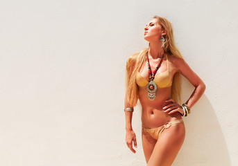 Sexy blond fashionable woman posing in a golden bikini