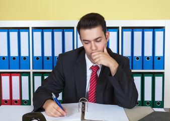 Junger Geschäftsmann im Büro arbeitet konzentriert
