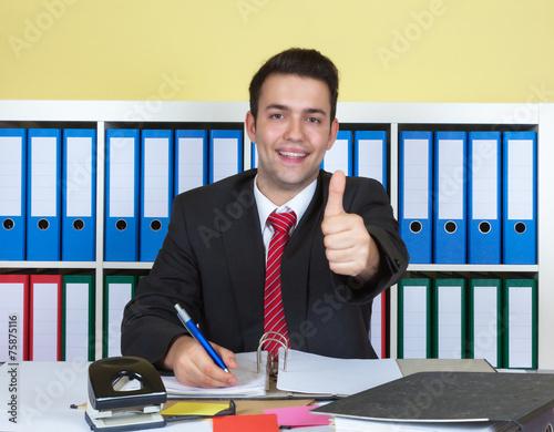 canvas print picture Lachender Geschäftsmann im Büro zeigt den Daumen