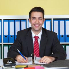 Sympathischer Geschäftsmann im Büro am Schreibtisch