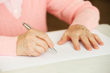 Hands of adult woman writing, on table, on light background