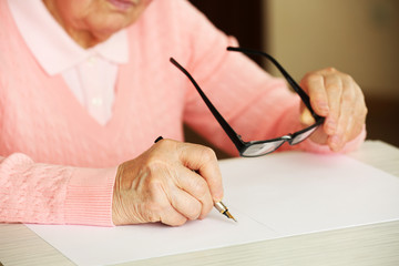 Hands of adult woman writing with pen and glasses,