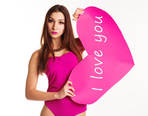 Beautiful girl in pink bodi holding paper heart
