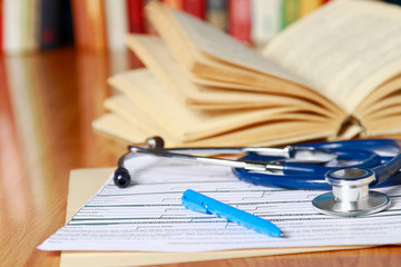 An image of a book, prescription and pen lying on the desk