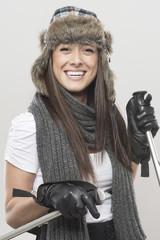 female beautiful skier hold ski sticks.shot on gray background.