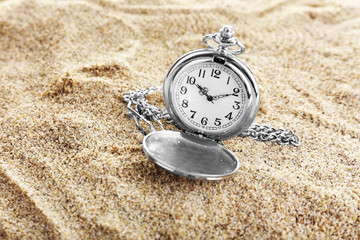 Silver pocket clock on sand background