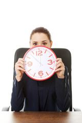 Businesswoman with big clock at the office