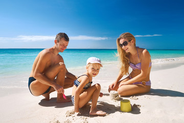 Family relaxing on tropical beach
