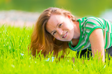 Portrait of charming girl in green t-shirt on the grass