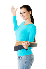 Woman holding open book and showing copyspace