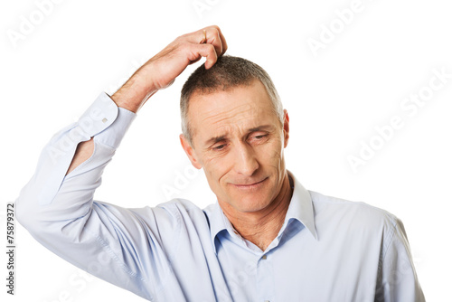 canvas print picture Confused man scratching his head