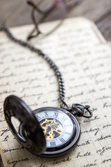 Vintage pocket watch on old book