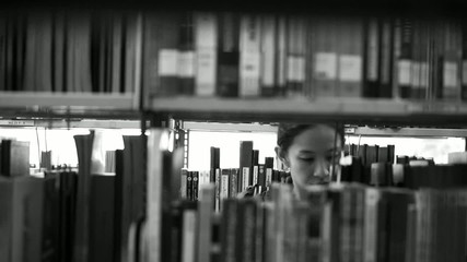 Female, girl student walking between shelves, searching for book