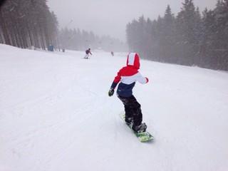 snowboarder beim fahren auf der skipiste