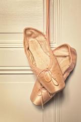 Old pink ballet shoes hanging, vintage process
