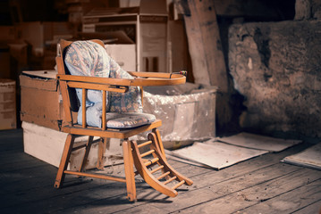 Old vintage baby chair in a dusty attic
