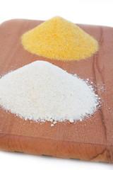 farina bianca e farina gialla su tagliere_ sfondo bianco