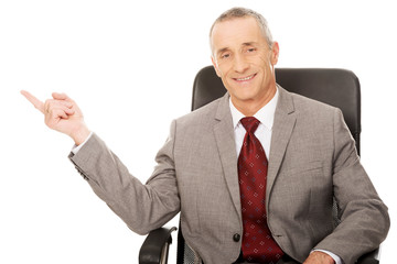 Businessman sitting on armchair and pointing