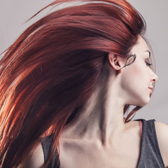 girl with flying hair over grey background