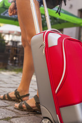 Young girl with red suitcase close-up. Travel concept.