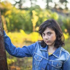 Black-haired teen girl in denim jacket portrait outdoors.
