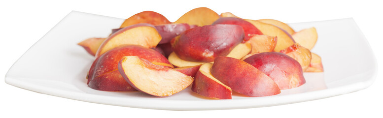 sliced peaches in a white dish isolated