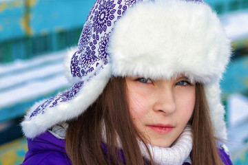 close up portrait of a cute little girl in winter hat with earfl