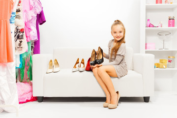 Girl trying to choose shoes among many