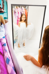 Beautiful little girl try dress before the mirror