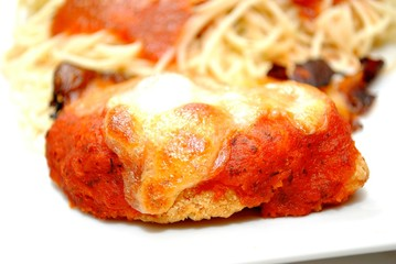 Close Up of Chicken Parmesan with Spaghetti in the Background