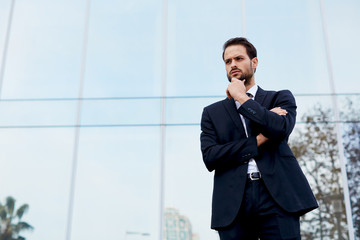 Pensive young businessman standing against office