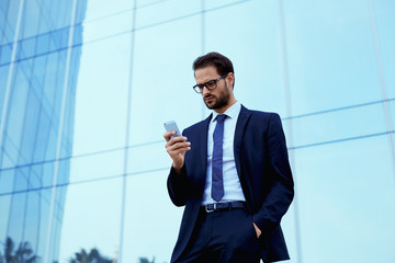 Confident businessman standing outside using phone