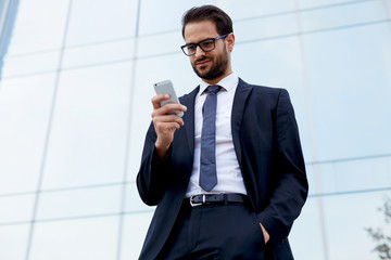 Handsome businessman looking at cell phone standing near office
