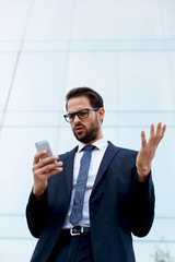 Businessman receiving shocking news read text message on phone