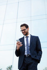 Happy businessman reading text message on cell phone
