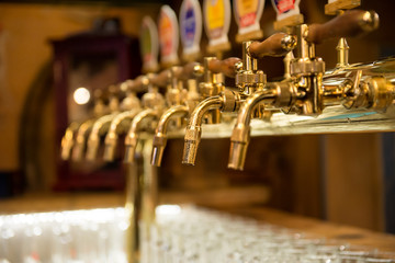 Different beer taps in a row.