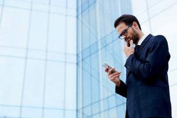 Confident young business man holding mobile phone